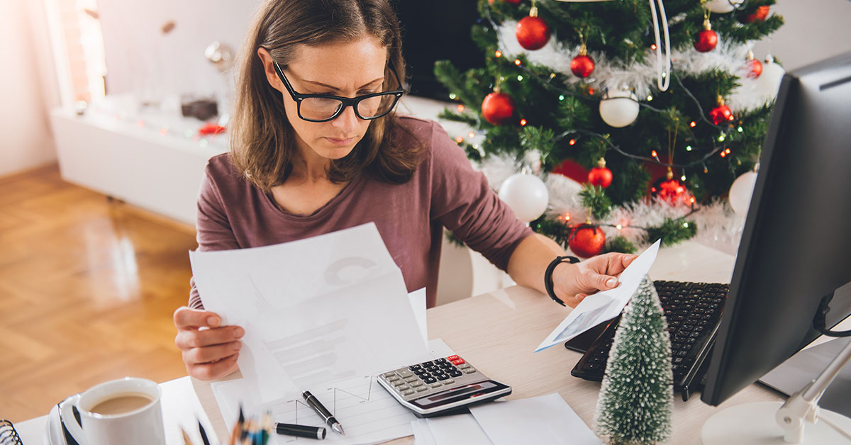 A woman sits at a desk in front of a Christmas tree. She is holding a stack of bills, looking at a calculator