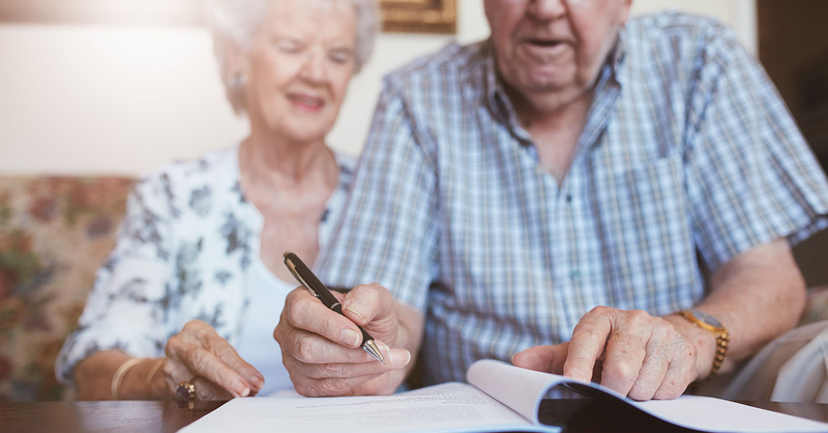 An elderly couple is sitting on a couch filling out paperwork
