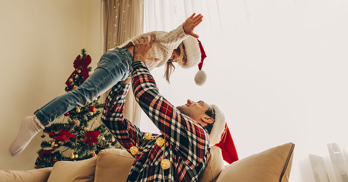 A father wearing a Santa hat is sitting on the couch holding his daughter up in the air. There is a Christmas tree behind them.