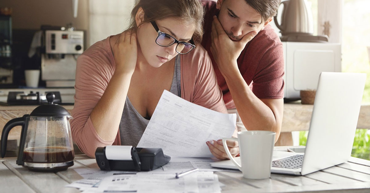 Stressed couple reviewing their tax forms