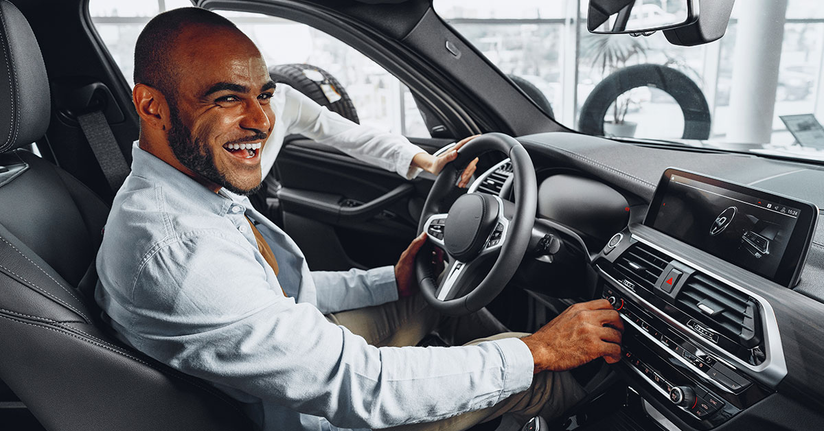 Inside the interior of a new car, a man sitting in the driver's seat has a bright smile as he looks toward the viewer.