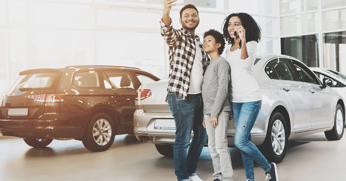 A young family stands in the showroom of a car dealership. The father is taking a selfie of the family in front of one of the cars.