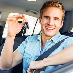 Happy young man with car keys in his hand