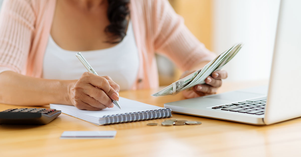 Close up of a woman's hands as she sits at a desk holding dollar bills in one hand and writing in a notebook with the other. On the computer is an open laptop, calculator, some change, and a credit card.