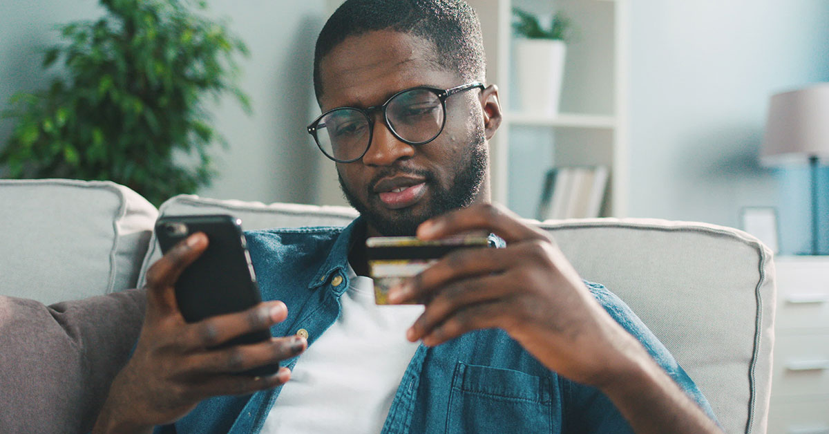 A man is sitting on a couch looking at his cell phone, which he is holding in his right hand. In his left hand, he is holding a credit card.