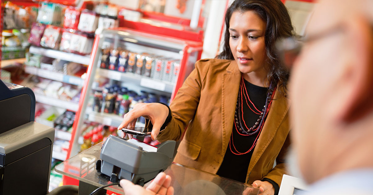 A woman is using her mobile phone to pay for a purchase at a convenience store.