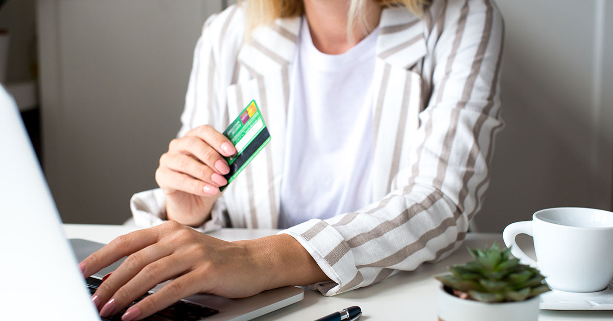 Close up of a woman sitting at a table. She is holding a credit card in one hand and typing on a laptop with her other hand. We do not see her head. On the table is a pen, a coffee cup and a succulent.