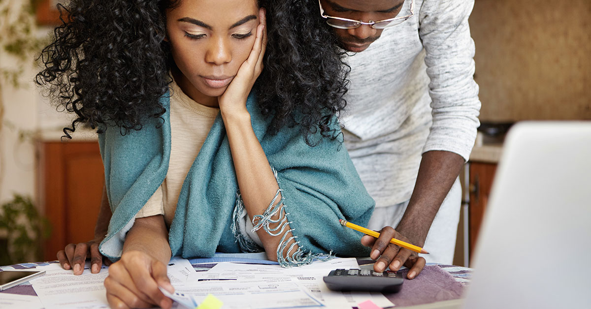 Photo of a young man and woman couple looking at a pile of bills scattered on a table. The woman is holding her head in her hand and sitting down. The man is standing behind her, leaning over and touching a calculator on the desk. They both have a neutral expression.