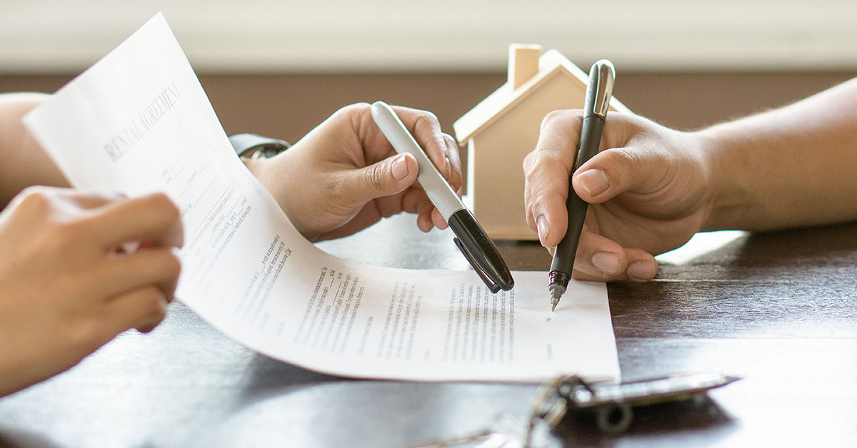 Photo close up of two people's hands as they go over a contract on a table. The person on the left is holding the contract and pointing to the signature line. The person on the right is holding a pen, signing the contract. On the table is also a set of keys and a plastic house.