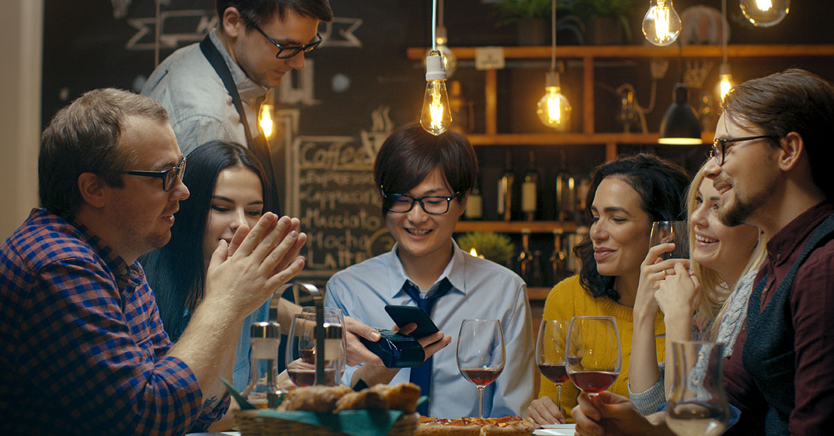 A group of thirty-something friends sit at a table in a restaurant having a conversation. The person in the middle is holding up their phone to a touchless pay machine being held by the waiter.