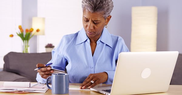 Older woman sitting at a table with computer, paperwork, and coffee mug. She is holding a pen and credit card.