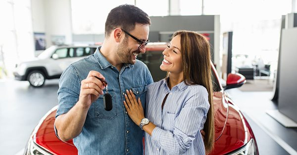 Happy couple standing in front of a red car in a car dealership. They are looking at each other, arms wrapped around each other. The man is holding up the keys to the car