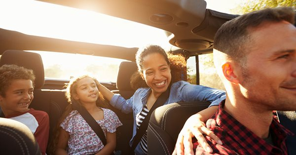 A close up view of a family in a car with the sunroof open. The sun is setting behind them. The father sits in the front seat and the mother is in the back seat with her two children, a son and daughter