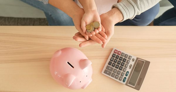Top down view of the hands of a man, woman, and young child gathered together holding a few coins. Below their hands is a table with a pink piggy bank and a calculator